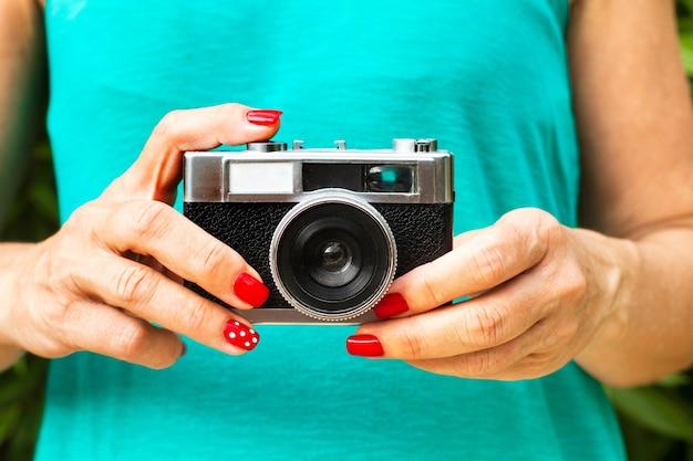 Mani della donna con i chiodi rossi che tengono una macchina fotografica fotografica dell'annata in una vista ravvicinata
