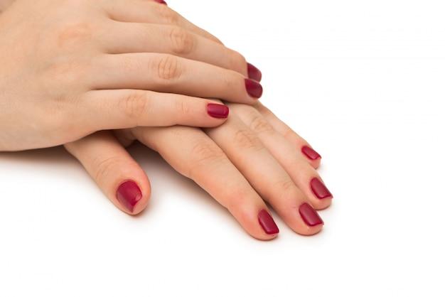 Mani della donna con il chiodo rosso isolato su bianco