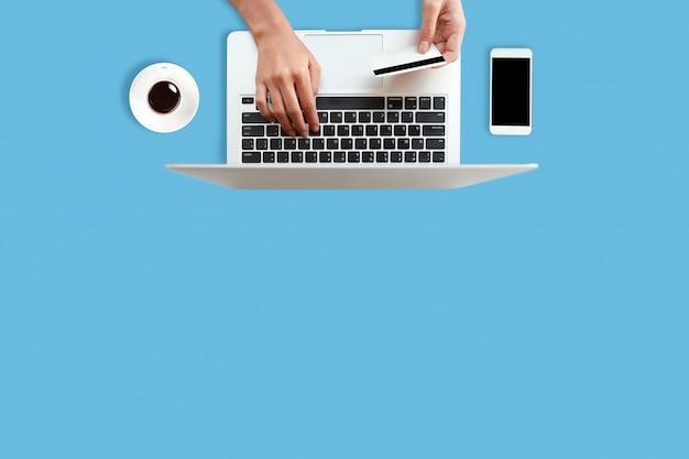 Mani della donna con il computer portatile facendo uso della carta di credito e del telefono cellulare sul blu