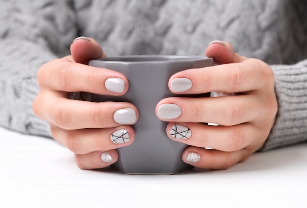 Mani della donna con il design delle unghie manicure geometrica in maglione accogliente