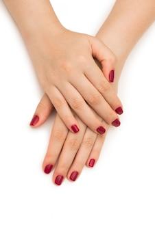 Mani della donna con l'unghia rossa isolata su bianco