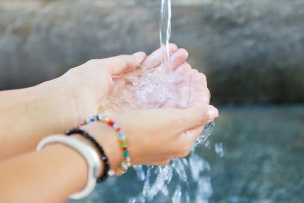Mani della donna con spruzzi d'acqua.