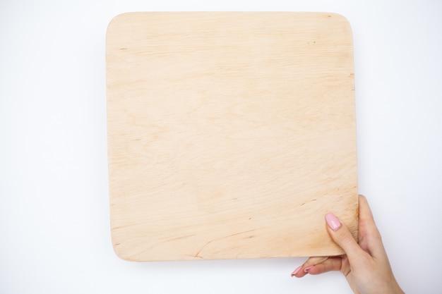 Mani della donna dell'ufficio che tengono un bordo di un albero su fondo bianco. copyspace. posto per il testo