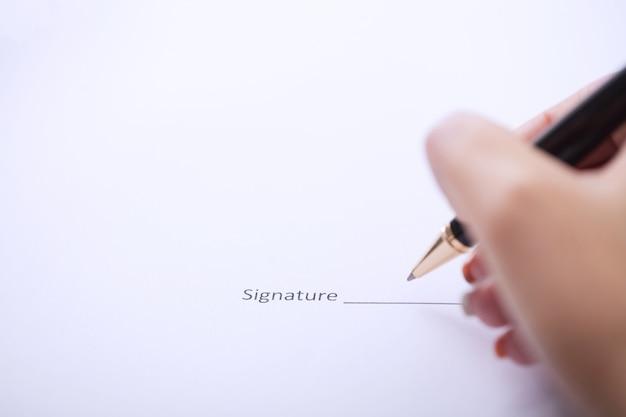 Mani della donna di affari che firma il documento di contratto