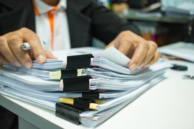 Mani della donna di affari che lavorano alle pile di archivi dei documenti per la finanza in ufficio