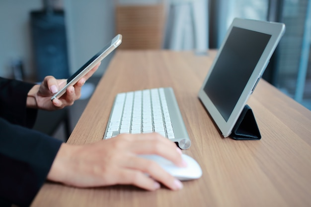 Mani della donna di affari facendo uso della tavola e del telefono cellulare