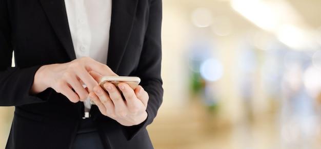 Mani della donna di affari facendo uso dello smart phone sopra l'ufficio della sfuocatura con il fondo della luce del bokeh, insegna, affare sul telefono