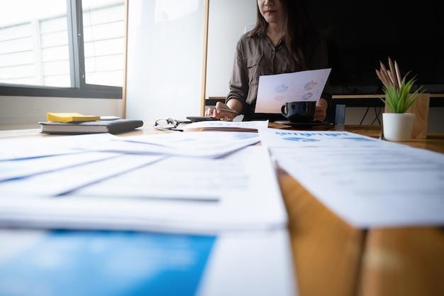 Mani della donna di affari o del ragioniere che tengono lavoro di ufficio con il calcolatore