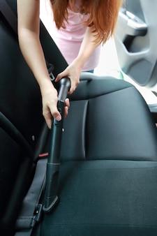 Mani della donna facendo uso dell'automobile interna dell'aspirapolvere