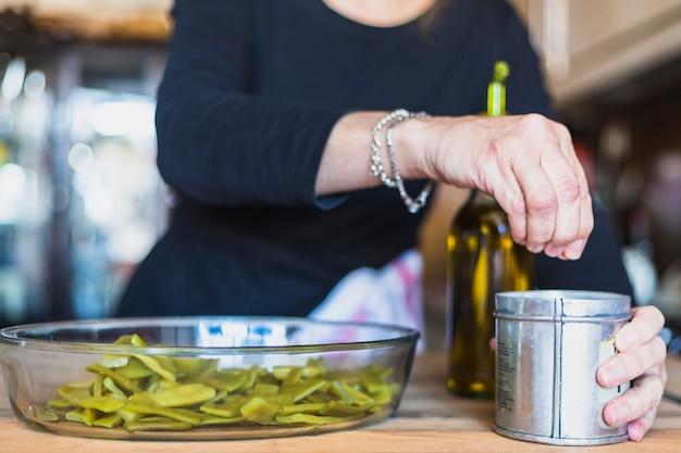 Mani della donna invecchiata che cucina nella cucina