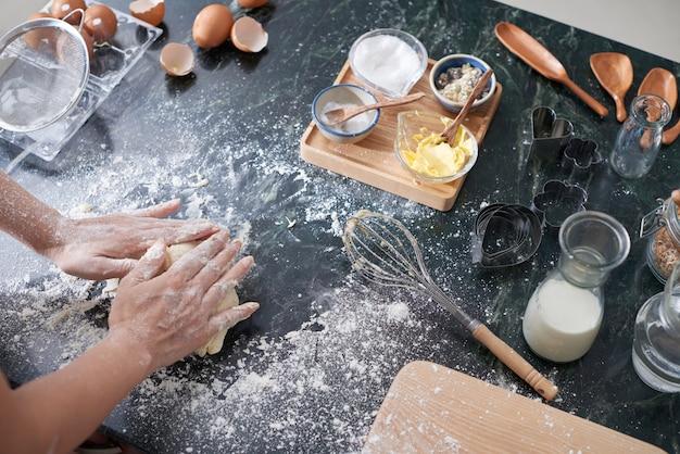 Mani della donna irriconoscibile che impastano pasta sul contatore di cucina a casa