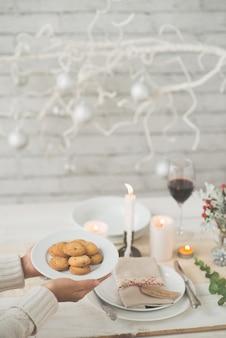 Mani della donna irriconoscibile che trasportano piatto di biscotti al tavolo da pranzo di natale