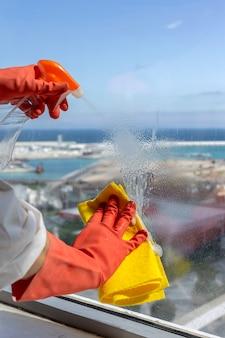 Mani della donna irriconoscibile con guanti protettivi per la pulizia della casa
