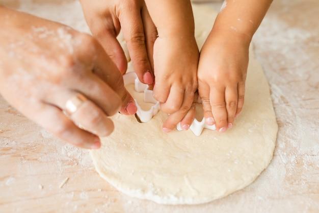 Mani della figlia e della madre che tagliano pasta per i biscotti