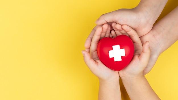 Mani della giornata mondiale della croce rossa, dell'adulto e del bambino che tengono cuore rosso