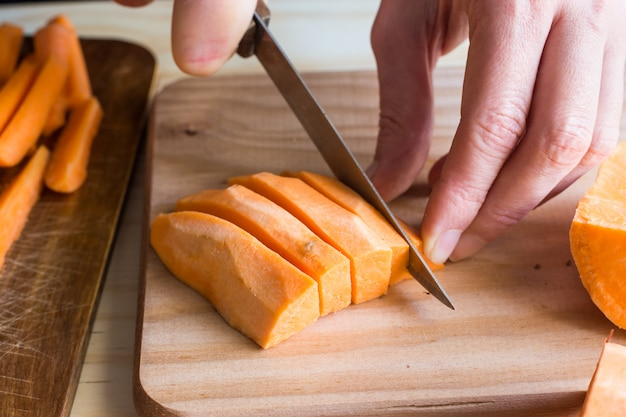 Mani della giovane donna che affettano le patate dolci nei cunei che preparano cena, bordo di legno, coltello