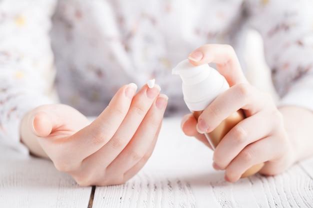 Mani della giovane donna che applicano crema idratante alla sua pelle