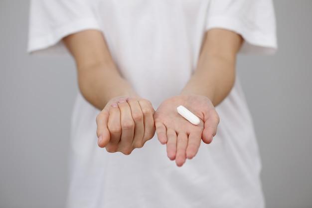 Mani della giovane donna che tengono diversi tipi di prodotti per l'igiene femminile - il tampone e una tazza mestruale sono conservati in mano