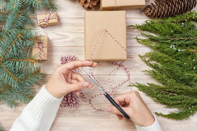 Mani della ragazza che avvolgono regalo di capodanno, processo di confezionamento regalo, cucito, creatività