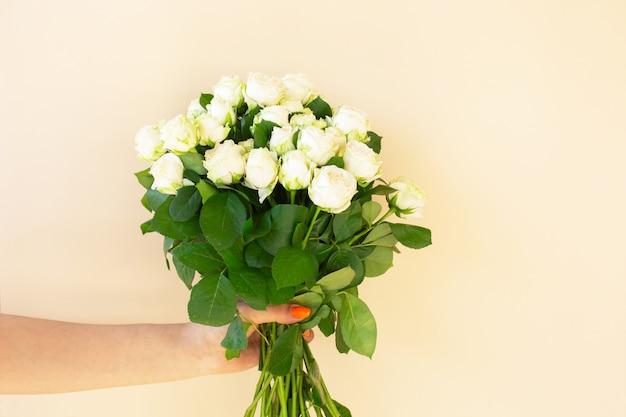 Mani della ragazza che tengono bellissimo bouquet di rose bianche su sfondo chiaro