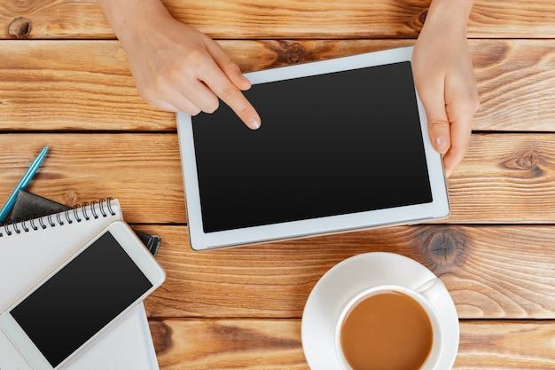 Mani della ragazza con tavoletta digitale e tazza di caffè su un tavolo di legno