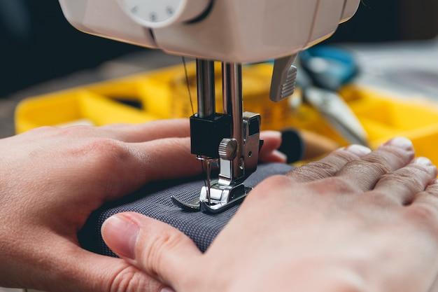 Mani della ragazza sulla macchina da cucire
