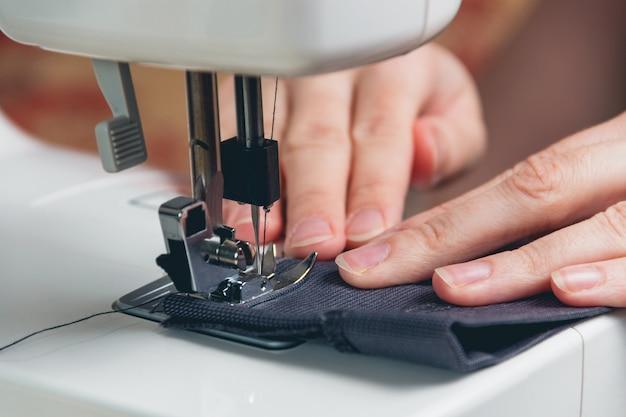 Mani della ragazza sulla macchina per cucire