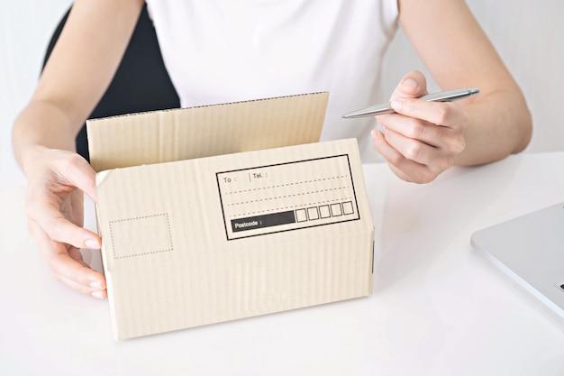 Mani della scrittura della donna sulla scatola di cartone alla tavola, lavorante a casa concetto