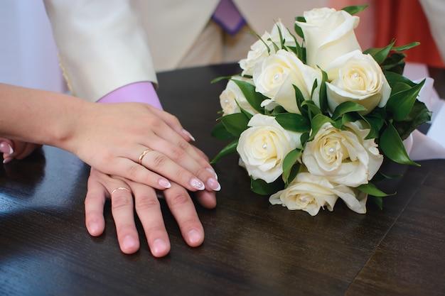 Mani della sposa e dello sposo con anelli d'oro al matrimonio