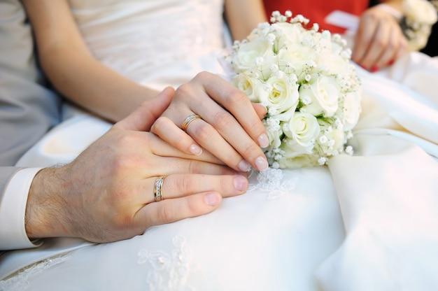 Mani della sposa e dello sposo con anelli e bouquet da sposa bianco