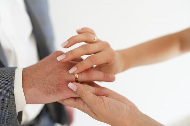Mani della sposa e dello sposo con anelli su bianco.