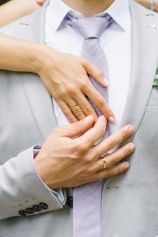 Mani della sposa e dello sposo con fedi nuziali.