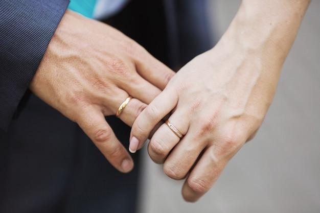 Mani della sposa e dello sposo con fedi nuziali