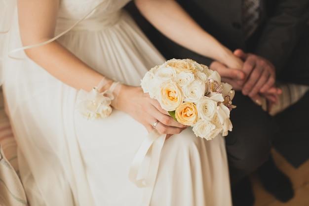 Mani della sposa e dello sposo sul bouquet da sposa.