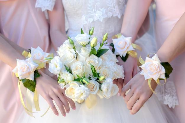 Mani della sposa e le sue damigelle con un mazzo di fiori