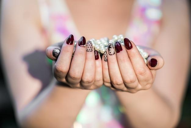 Mani delle belle donne che tengono perla