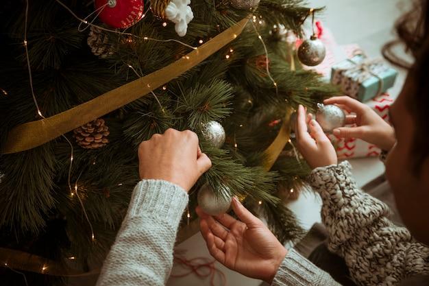 Mani delle coppie che mettono i giocattoli sull'albero di natale
