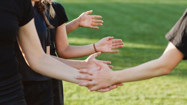 Mani delle donne che salutano prima di una partita