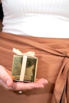 Mani delle donne che tengono il contenitore di regalo dell'oro, regalo di festa, compleanno, natale, padre o madre, primo piano di san valentino
