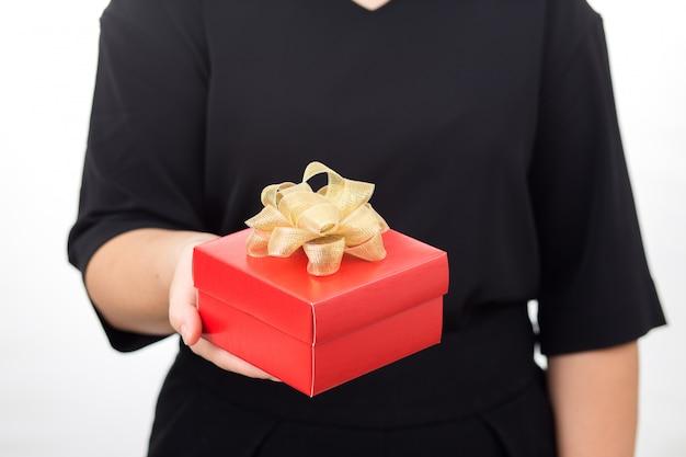 Mani delle donne che tengono il contenitore di regalo rosso. donne che fanno attenzione al vestito nero su fondo bianco