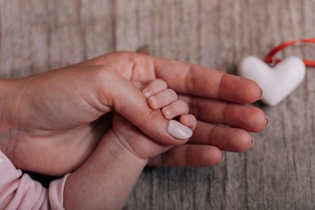 Mani delle donne che tengono la mano del bambino con un cuore. il concetto di maternità, cura, famiglia, protezione, amore.