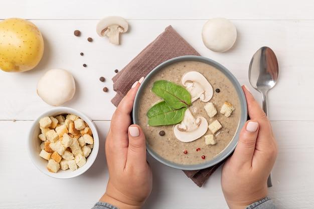 Mani delle donne che tengono una ciotola grigia di crema di zuppa di fungo su fondo rustico leggero