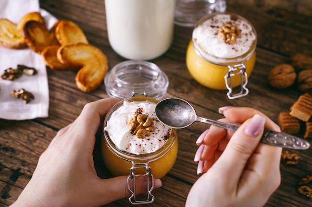 Mani delle donne con un cucchiaio. frappè di zucca in barattolo di vetro con panna montata, caramella mou, noci e biscotti al miele