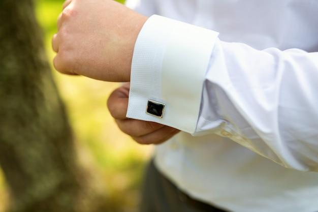 Mani dello sposo di nozze che si preparano in vestito. uomo sta preparando per il lavoro.