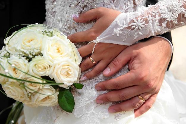 Mani dello sposo e della sposa con fedi nuziali e bouquet di rose