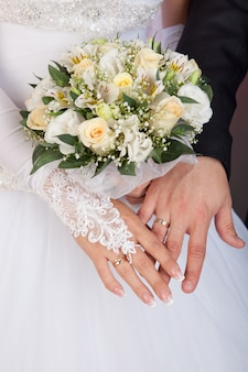 Mani dello sposo e della sposa con fedi nuziali e mazzo di rose