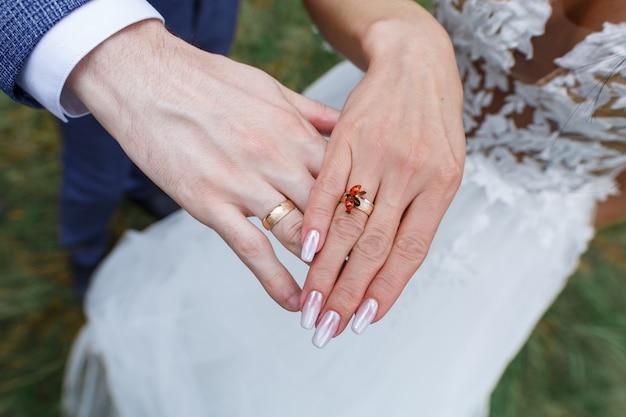 Mani dello sposo e della sposa con gli anelli di cerimonia nuziale dorata. due anelli di nozze d'oro sulle dita degli sposi. scarabeo rosso sulla mano di una giovane donna da vicino. giorno del matrimonio. concetto di storia d'amore
