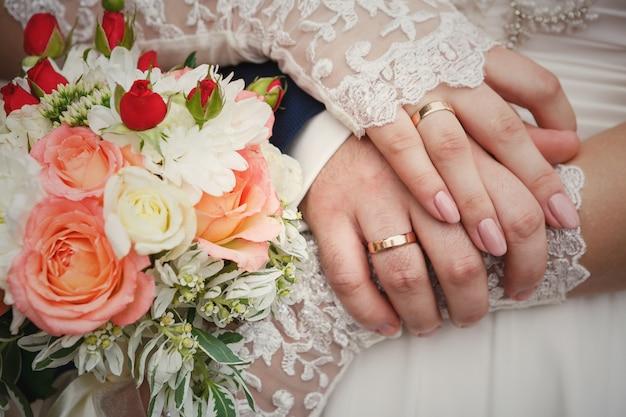 Mani dello sposo e della sposa con il mazzo e gli anelli di nozze