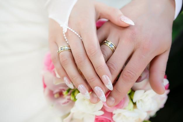 Mani dello sposo e la sposa con fedi nuziali e un bouquet da sposa di rose