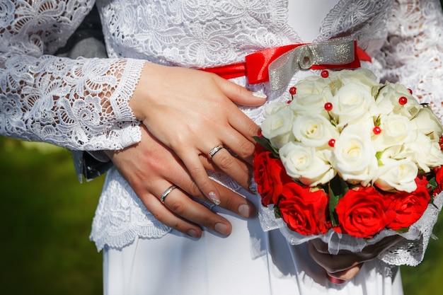 Mani dello sposo e la sposa con fedi nuziali e un mazzo di rose beige